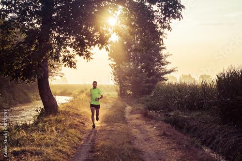 Leinwand Poster Ragazzo che corre all'alba su strada di campagna in estate