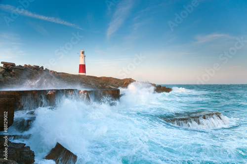 Stormy seas crash over the rocks with the lighthouse in the background at Portland Bill in Dorset Fototapet