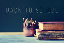 Pencils, Old Books And The Text Back To School On A Chalkboard,