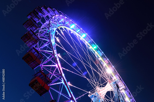 Poster Attraction parc Ferris wheel with multi-colored illumination against night sky
