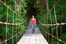 Happy Woman Hiker Crossing Suspension Bridge