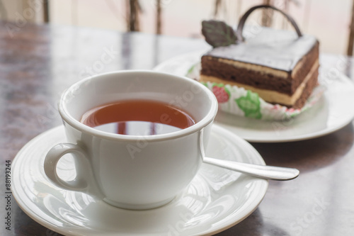 Photo  White cup of tea and cake in the cafe