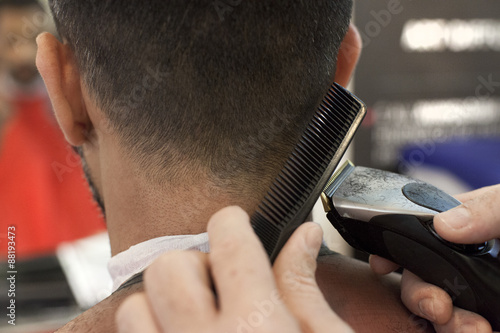 Un parrucchiere mentre taglia i capelli Poster