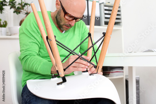 Fotografie, Tablou  Heimwerker baut ein Stuhl zusammen
