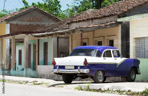 Photo  HDR Kuba Ansicht eines blauen amerikanischen Oldtimers vor einem Haus