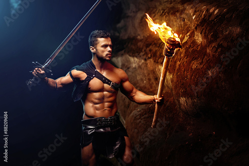 Foto  Spartan auf einem dunklen Hintergrund schaukelt, Krieger, Fighte hält eine Rais
