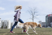 Side Profile Of Teenage Girl Walking In Park With Dog, Munich, Bavaria, Germany