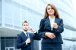 Successful young business woman showing thumbs up sign standing in front of his office.