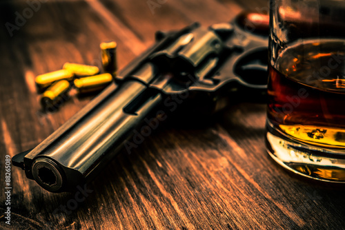 Glass of whiskey with revolver on the wooden table Canvas Print