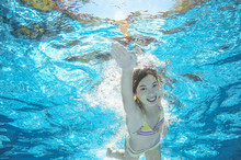 Child Swims In Pool Underwater, Happy Active Girl Has Fun In Water