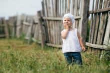 Little Girl And Wooden Fence