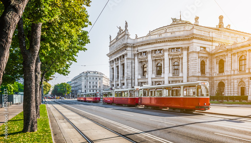 Montage in der Fensternische Eisenbahnschienen Wiener Ringstrasse with Burgtheater and tram at sunrise, Vienna, Austria