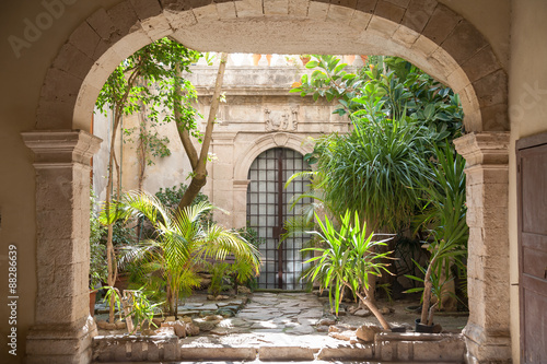 Foto Courtyard of an old baroque palace and plants in the old Syracuse