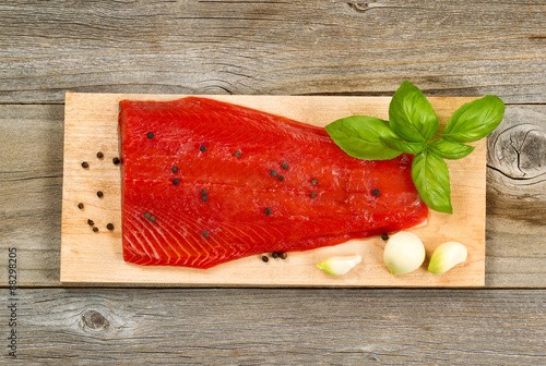 Photo  Fresh red salmon fillet on cedar cooking plank with spices and h