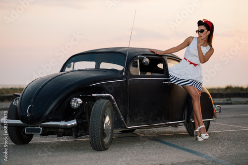 fototapeta na ścianę Beautiful pin-up girl posing with hot road car