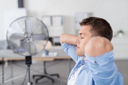 Fotografie, Obraz  geschäftsmann im büro mit ventilator im hintergrund