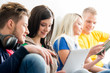 Group of students on a break. Focus on a girl using tablet. Background is blurry.