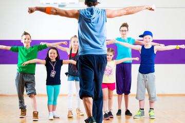 Dance teacher giving kids Zumba fitness class