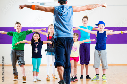Fotobehang Dance School Dance teacher giving kids Zumba fitness class