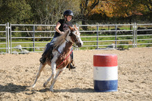 Young Girl Galloping Around A Barrel During A Barrel Race