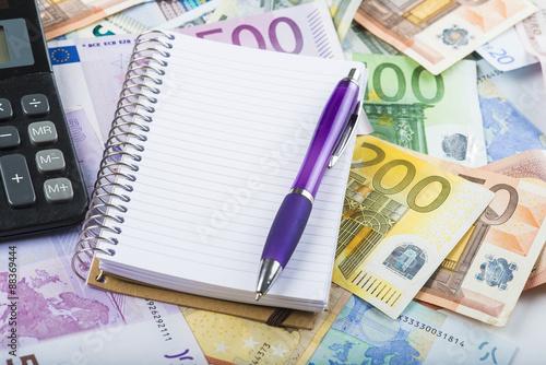 Fotografía  Libreta en blanco con espacio para texto sobre un fondo de billetes calculadora