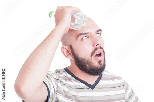 Valokuva  Man cooling his head with cold water in plastic bottle
