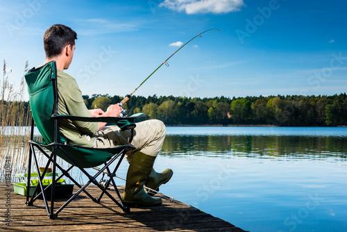 Fototapeta Mann beim Angeln am See sitzt auf Steg