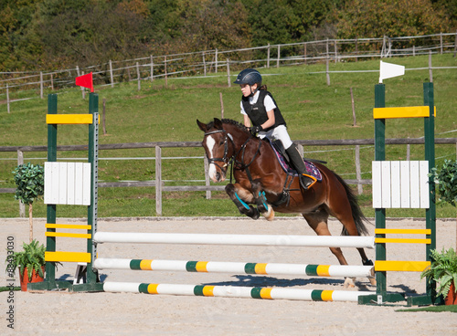 Fotografering Girl and pony jumping over hurdle on showjumping competition