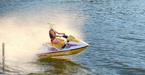 Poster Nautique motorise Adult having fun jumping a wave riding yellow and white Sea Doo jet ski in California Ocean