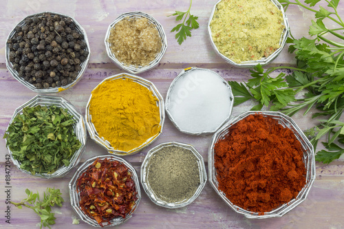 Photo  Set of various spices in shiny bowls on a purple colored wooden