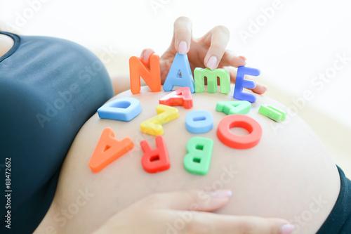Fotografía  Mujer embarazada joven con el nombre de bloques de la letra de ortografía en su