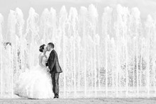 Bride And Groom Kissing In Front Of Water Fountain Black And Whi