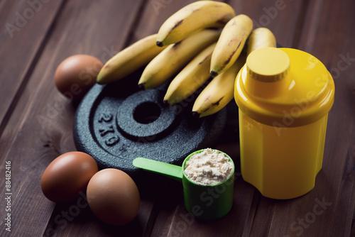 Fotografie, Obraz  Shaker, odměrka s proteinem, vejce a banány, close-up