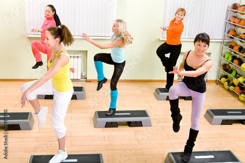 Fotografie, Obraz  Women Different Nationalities Doing Step Aerobics in the Gym