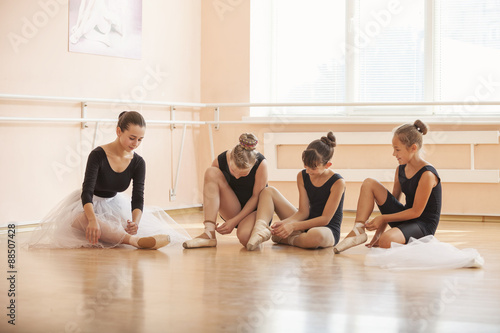 Fényképezés  Young ballerinas putting on pointe shoes while sitting on floor in ballet class