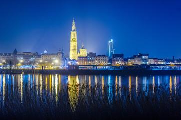 Noćni pogled na osvijetljeni grad Antwerpen u Belgiji snimljen sa suprotne obale rijeke scheldt / schelde.