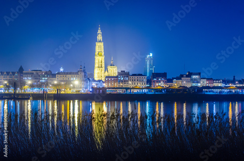 Night view over illuminated city of antwerp in belgium taken from the opposite shore of the river scheldt/schelde.