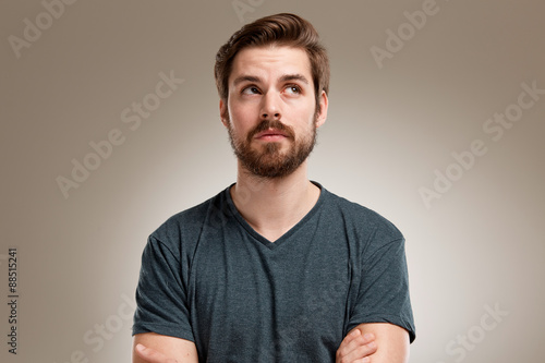 Fotografering  Portrait of young man with beard, looking up