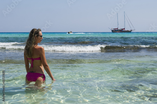 In de dag Bleke violet Blond girl looks sailing ship sea blue and green to the beach