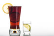Glass of cola with sliced lemon and shot of vodka
