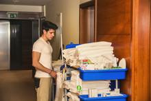 Young Man Pushing A Housekeepi...