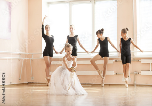 fototapeta na drzwi i meble Little girl dancing with pointe shoes, older classmates warming up at the barres