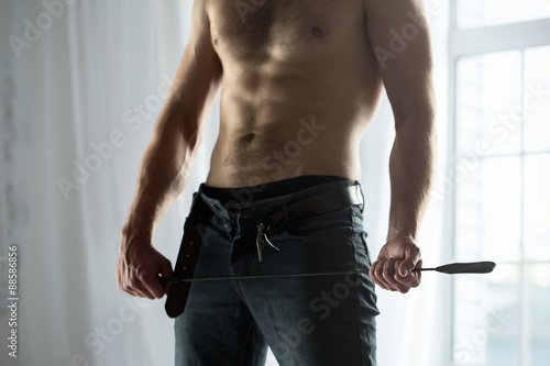 Photo  Handsome guy topless with whip BDSM