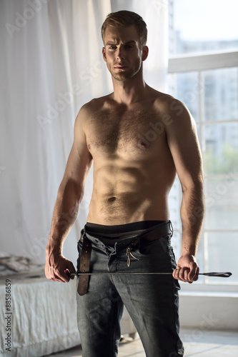 Obraz na plátne Handsome guy topless with whip BDSM