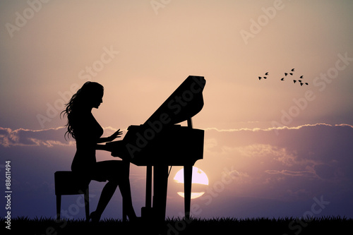 Fotografie, Obraz  woman plays the piano at sunset