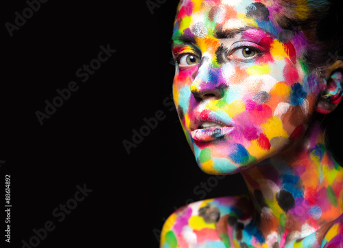 Girl with colored face painted. Art beauty image. Poster