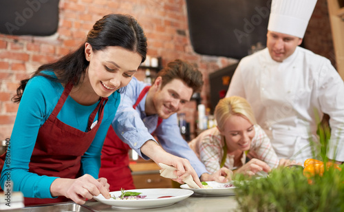 Foto  happy friends and male chef cooking in kitchen