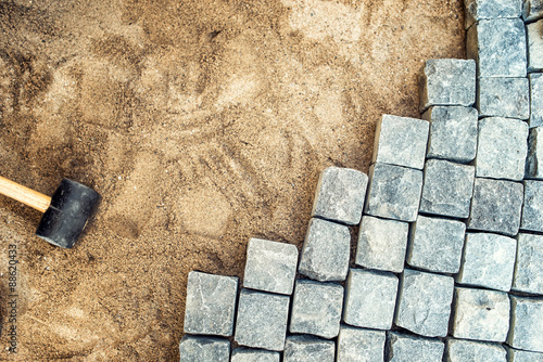 Construction tools and details, pavement installing and rocks. Granite stones laying on sand, making of pavement