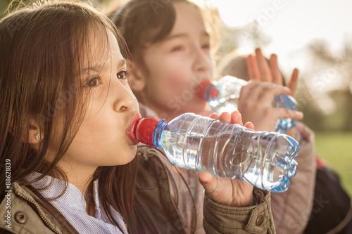 Fotografía  Photo of two girls drinking water from PET bottle