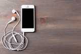 Mobile phone and earphones on wooden background